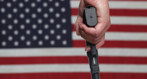 Man-holds-gun-in-front-of-US-flag-via-Shutterstock-800x430